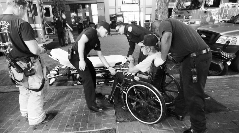 Paramedics prepare to place San Diego's top user of 911on a gurney on Fifth Avenue in downtown San Diego on Tuesday evening.