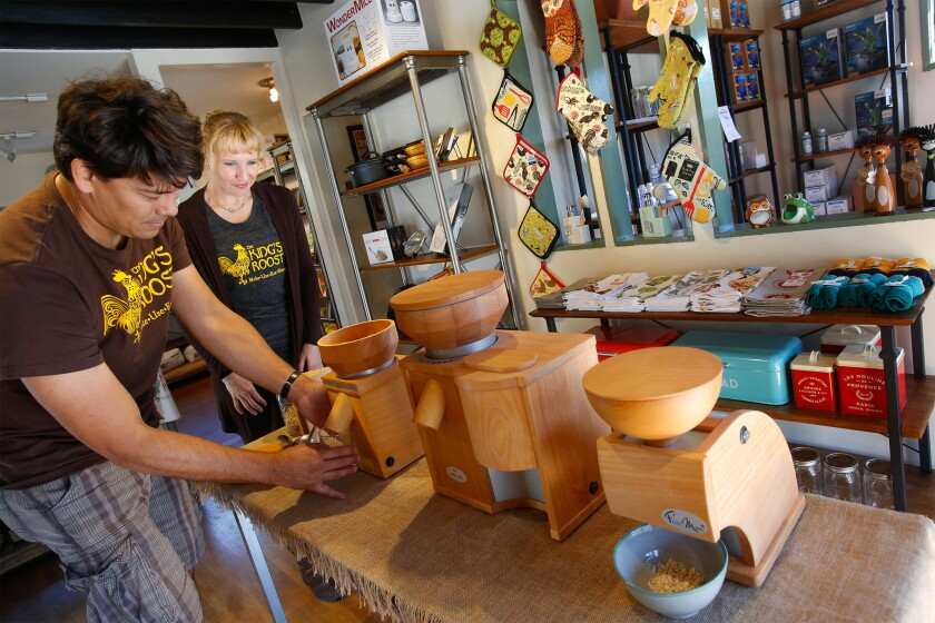 Roe Sie, left, demonstrates a grain mill as his wife, Trish Sie, looks on at King's Roost, a new homesteading store in Los Feliz.
