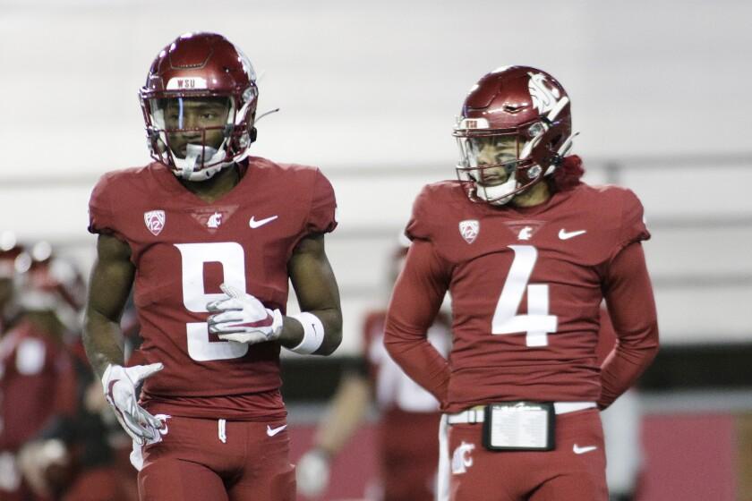 Washington State wide receiver Renard Bell and quarterback Jayden de Laura stand on the field.