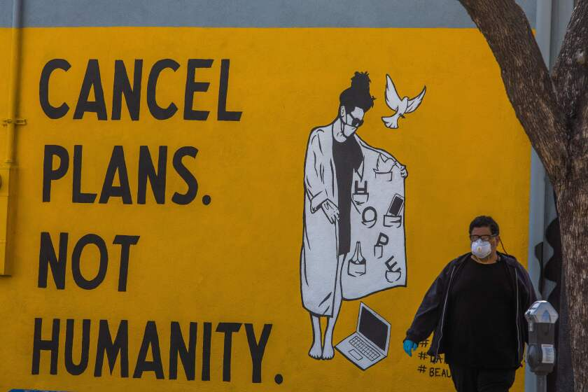 A man wearing gloves and a face mask walks by a mural in L.A. on Saturday.