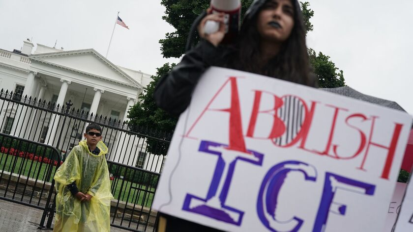 An immigrant rights activist protests outside the White House on June 22.