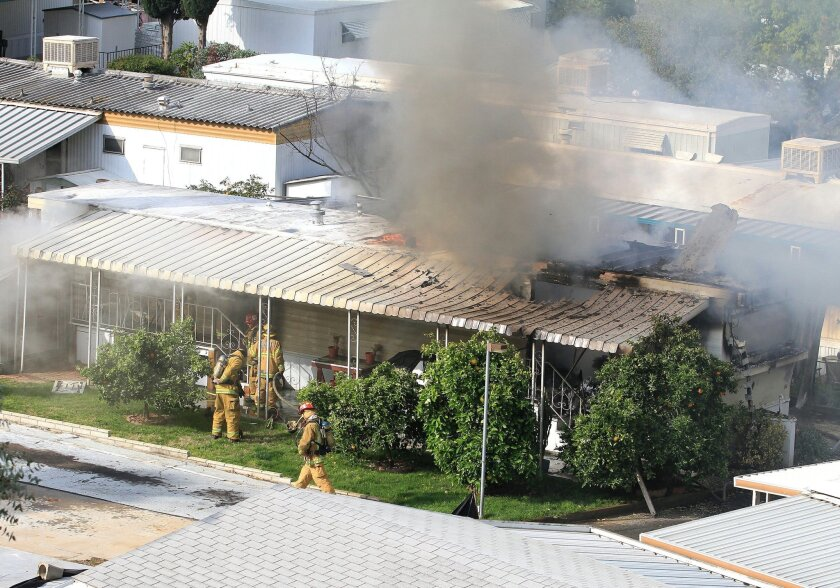 Firefighters gain entry to a mobile home at the Starlight Mobile Home Park in El Cajon Tuesday, March 27th at 9 a.m.