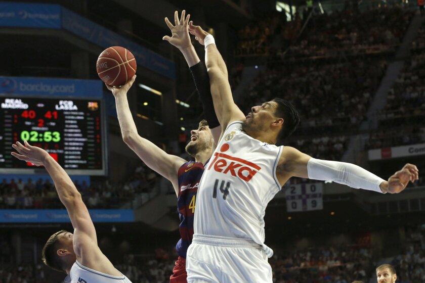 El pívot croata del FC Barcelona Lassa Ante Tomic (c) lucha un rebote con el mexicano Gustavo Ayón (d), del Real Madrid, durante el cuarto partido de la final de la Liga ACB que se juega hoy en el Palacio de los Deportes de Madrid.