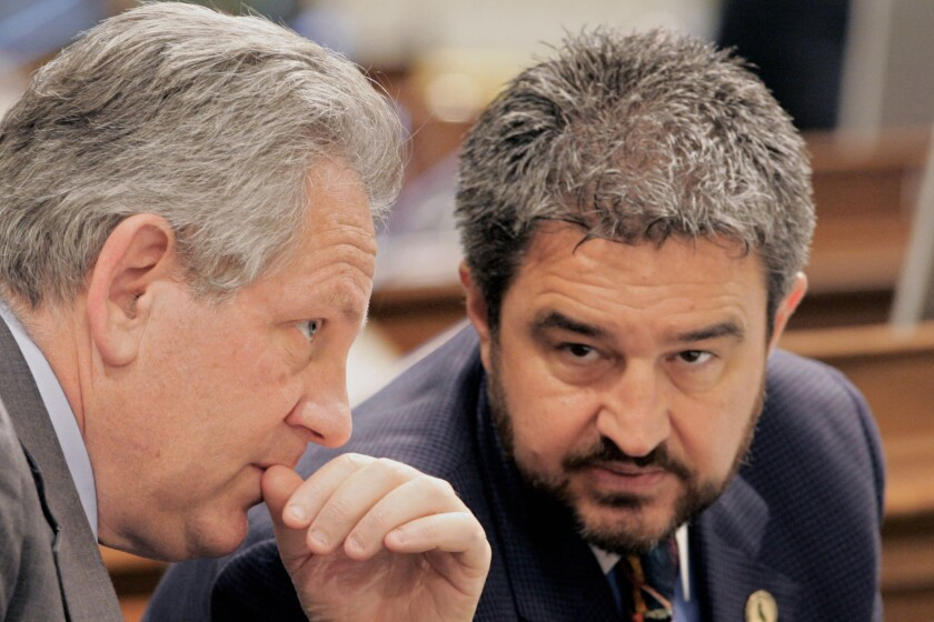 FILE - In this May 26, 2005, file photo, Assembly members Joe Canciamilla, D-Pittsburg, right, and Keith Richman, R-Chatsworth, left, confer during a debate at the Capitol in Sacramento, Calif. Contra Costa county prosecutors announced Tuesday, July 13, 2021, that Canciamilla has been sentenced to a year in jail after he pleaded guilty to nine counts of grand theft and perjury for using more than a quarter-million dollars of campaign funds on personal expenses during this time as elections chief for Contra Costa County and lying about it. (AP Photo/Rich Pedroncelli, File)