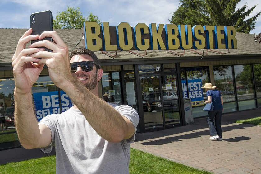 Scott Thornton takes a selfie in front of the Bend, Ore., Blockbuster on Friday, July 13, 2018. The Bend store is the last remaining Blockbuster in operation in the United States after two stores in Alaska closed earlier this week.
