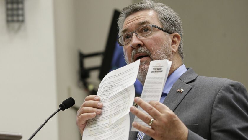 Assembly Rules Committee Chairman Ken Cooley displays sexual harassment documents during a hearing in Sacramento in November.