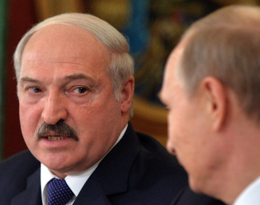 Belarus President Alexander Lukashenko, left,  visits with Russia's Vladimir Putin.