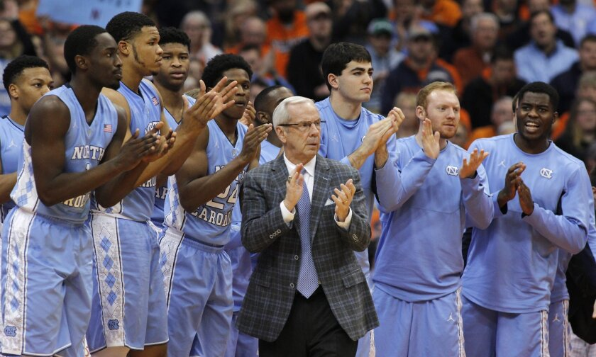 FILE - In this Jan. 9, 2016, file photo, North Carolina head coach Roy Williams claps with players on the bench during the second half of an NCAA college basketball game against Syracuse in Syracuse, N.Y. No. 2 North Carolina is the only unbeaten team in the Atlantic Coast Conference after a favorable opening month of the league schedule. The Tar Heels on Saturday play Boston College, which is 0-7 in the league. Then things get tougher. (AP Photo/Nick Lisi, File)
