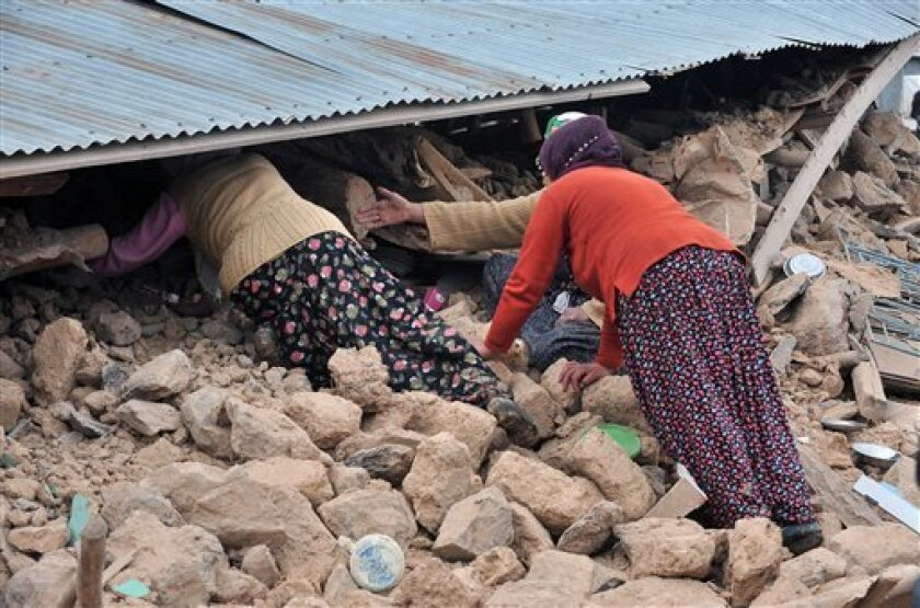 Women search for family members trapped in the debris of  a destroyed house in Okcular village in the eastern province of Elazig, Turkey, Monday, March 8, 2010, hours after a strong earthquake, with a preliminary magnitude of 6, hit eastern Turkey early Monday, killing scores of people and knocking