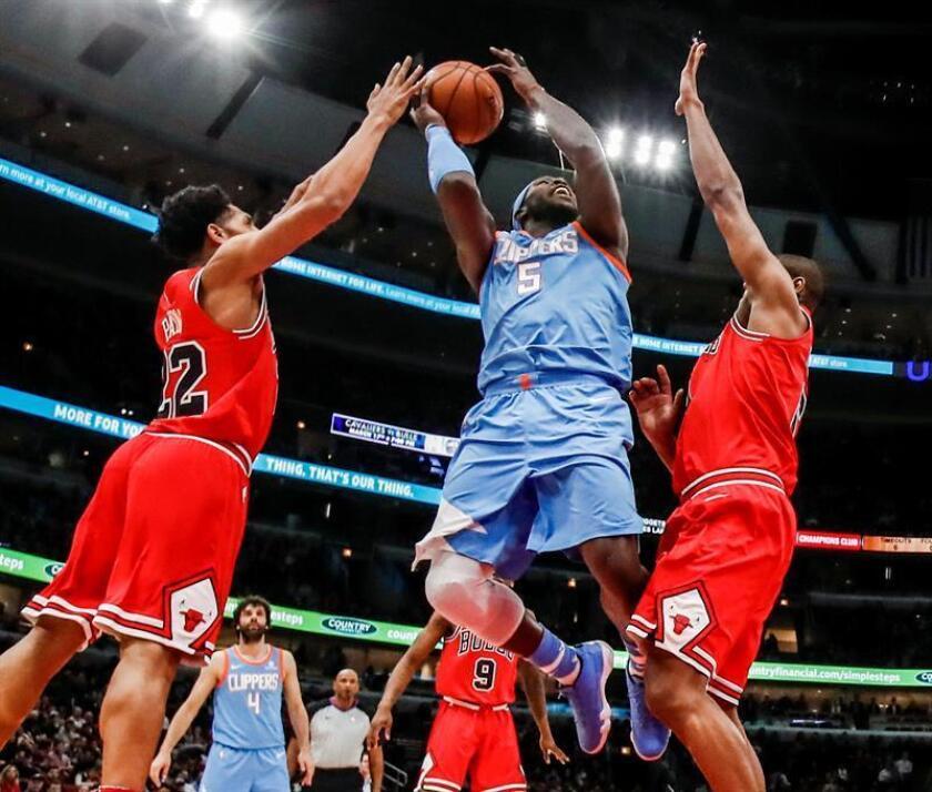 El escolta Cameron Payne (i) y el alero brasileño Cristiano Felicio (d) de Chicago Bulls en acción ante el alero Montrezl Harrell (c) de Los Ángeles Clippers hoy, martes 13 de marzo de 2018, durante un juego entre Los Ángeles Clippers y Chicago Bulls de la NBA, en el United Center en Chicago, Illinois (Estados Unidos). EFE