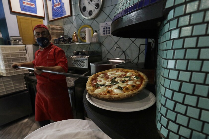Eugenio Iorio wears a face mask to curb the spread of COVID-19 as he bakes a pizza at a restaurant in Naples, Italy, Saturday, Nov. 14, 2020. The regions of Campania and Tuscany were designated red zone on Friday, signaling the dire condition of a hospitals struggling with a surge of new admissions. (AP Photo/Gregorio Borgia)
