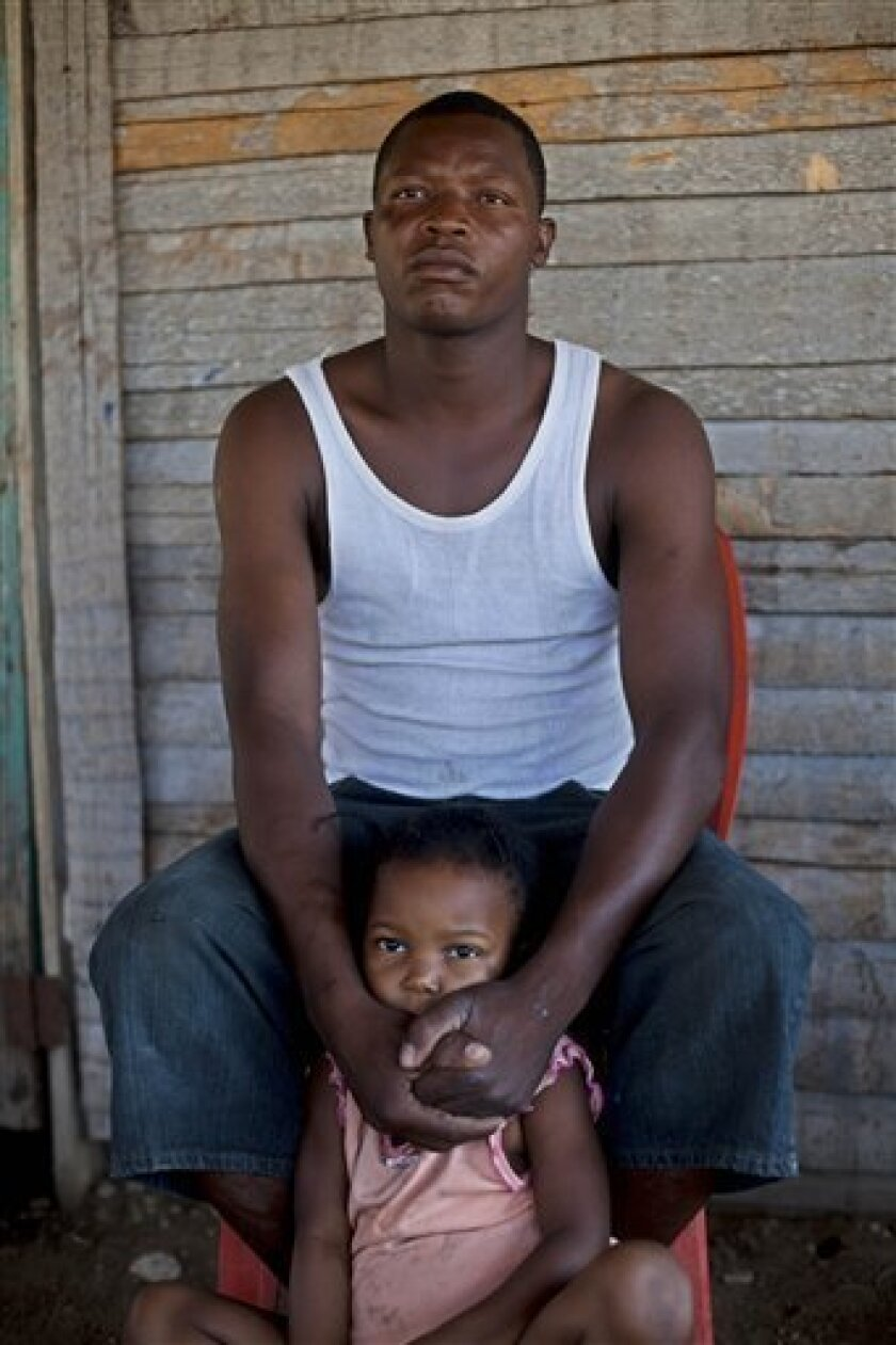In this photo taken on Jan. 29, 2011, Erickner Auguesten, a 36-year-old father of three children that has lived illegally in the Dominican Republic since 1991, sits with his daughter during an interview with The Associated Press in Jimani, Dominican Republic.  Auguesten said immigration agents stop