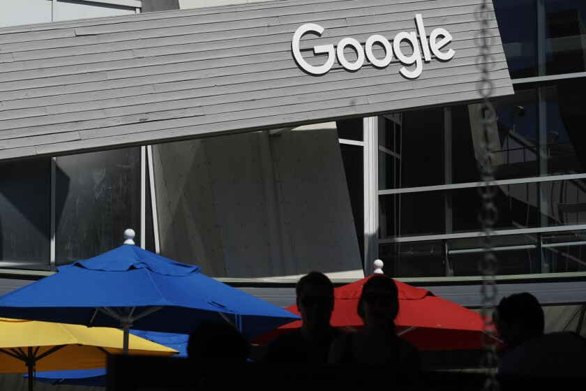 FILE - In this Sept. 24, 2019, file photo people walk by a Google sign on the campus in Mountain View, Calif. USA., The coalition of technology and publishing companies, Marketers for an Open Web said Monday Nov. 23, 2020, they have asked U.K. competition watchdog to investigate Google's plans to revamp its ad data system, saying the changes would cement the U.S. tech giant's online dominance. (AP Photo/Jeff Chiu, File)
