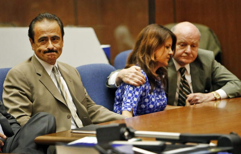 Former Los Angeles City Councilman Richard Alarcon, left, reacts as his wife, Flora Montes de Oca Alarcon is comforted by her attorney Mark E. Overland, right, as verdicts are read on voter-fraud and perjury charges.
