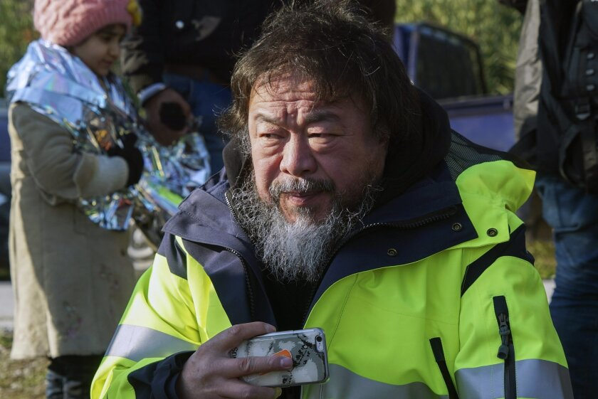 Chinese activist and artist Ai Weiwei assists refugees and migrants after their arrival on a dinghy from the Turkish coast to a beach near Mytilene port on the northeastern Greek island of Lesbos on Thursday, Jan. 28, 2016. Despite toughening European border controls, refugees and migrants have continued to travel to the Greek islands near the Turkish coast, at a rate of roughly 1,500 per day since the beginning of the year, braving the bad weather in dinghies and old wooden boats.(AP Photo/Mstyslav Chernov)