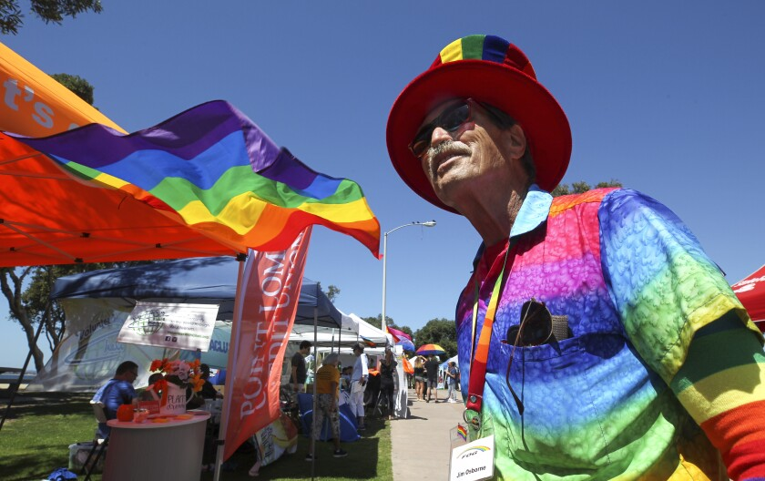 Jim Osborne, or Mister Rainbow, stands next to a rainbow flag during the South Bay Pride Art and Music Festival at Bayfront Park on Saturday, Sept. 14, 2019 in Chula Vista.