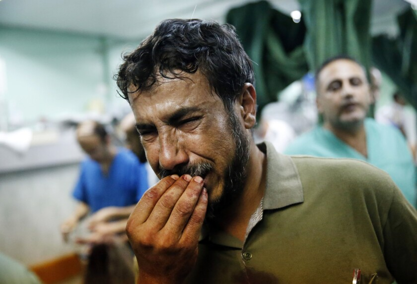 A Palestinian man cries after bringing a child, wounded during fighting between Israeli forces and Hamas militants, to the emergency room room.