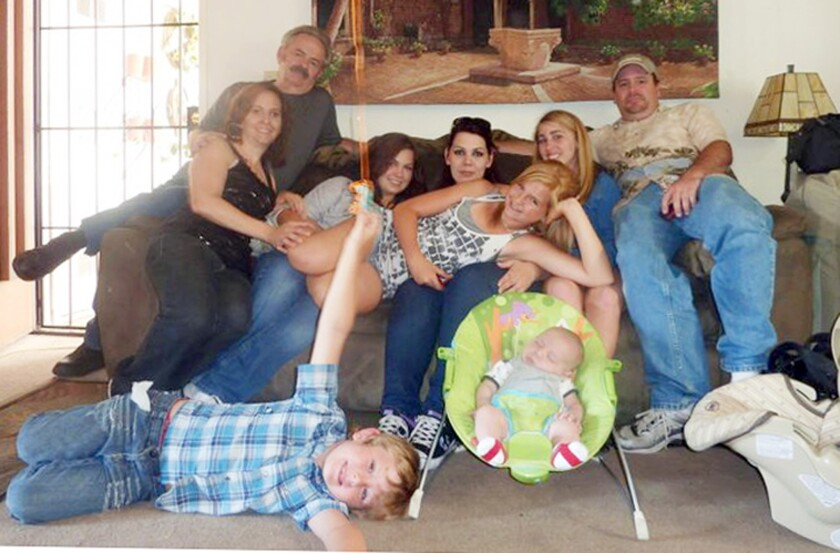 Members of the extended Anderson and Saincome families, with James Lee DiMaggio, right, are seen in this June 2011 photo provided by Andrea Saincome. Seated from left are Christina Anderson, Christopher Saincome, Christina's sisters Samantha Saincome and Andrea Saincome, their niece Hannah Anderson (reclining), Alexi (last name unavailable, friend of Hannah's), and DiMaggio. On the floor are Ethan Anderson, left, and Andrea's infant child.