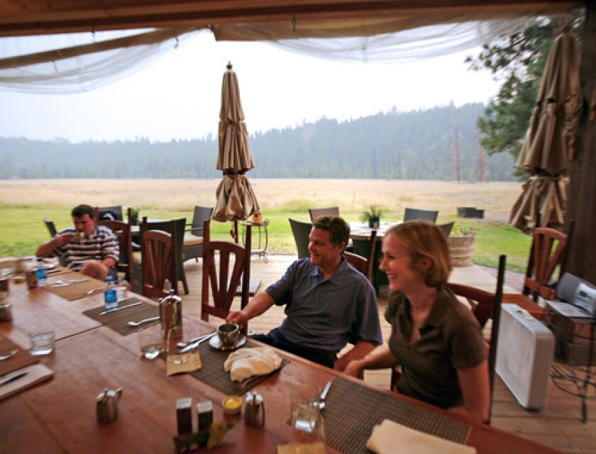 Greg Bondick, left, of Carlisle, Mass., and Rhyne and Lisa Davis of Charlotte, N.C., enjoy coffee and conversation at The Resort at Paws Up, a 37,000-acre getaway in Montana. The resort is for affluent travelers who want to enjoy the outdoors but can't fathom using an outhouse.