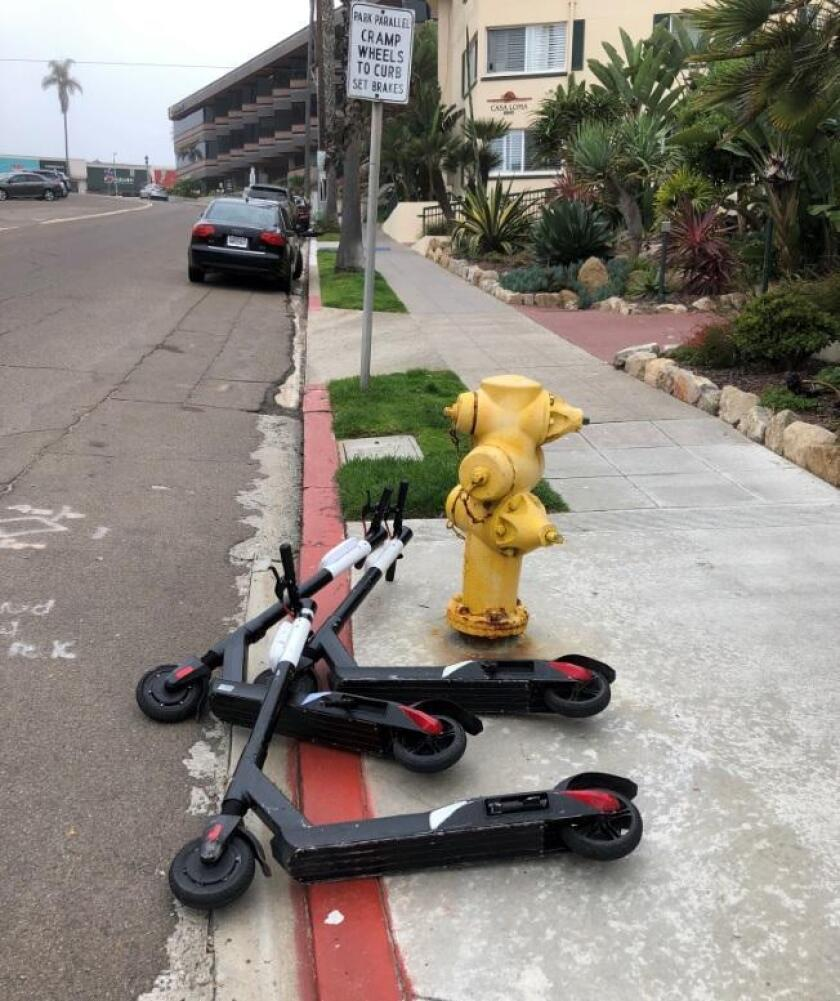 Knocked-down electronic scooters are blocking sidewalks and spotted along a street in La Jolla last week.