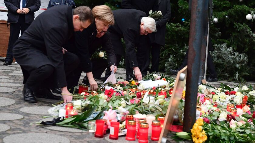 From left, Berlin Mayor Michael Mueller, German Chancellor Angela Merkel, Interior Minister Thomas de Maiziere and Foreign Minister Frank-Walter Steinmeier lay flowers on Dec. 20, 2016, at the site of an attack on a Christmas market in Berlin.
