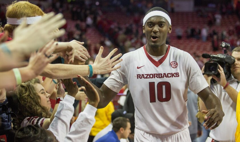 FILE - In this Jan. 22, 2015, file photo, Arkansas forward Bobby Portis, right, celebrates with students after his game-winning shot in overtime of an NCAA college basketball game against Alabama in Fayetteville, Ark. Portis, this Southeastern Conference Player of the Year, says he is declaring for the NBA draft after his standout sophomore season. (AP Photo/Gareth Patterson, File)