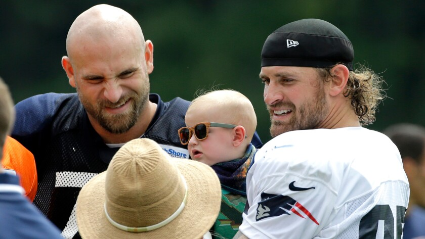 New England defensive end Chris Long, right, holds his 5-month-old son, Waylon, while spending time with his brother, Chicago Bears offensive tackle Kyle Long, at training camp on Aug. 16.