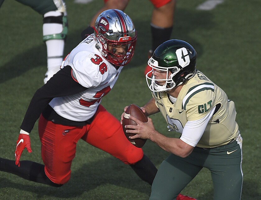 Charlotte quarterback Chris Reynolds, right, scrambles out of the pocket looking to pass as he is chased by Western Kentucky linebacker Kyle Bailey, left, during the second half of an NCAA college football game on Sunday, Dec. 6, 2020. (Jeff Siner/The Charlotte Observer via AP)
