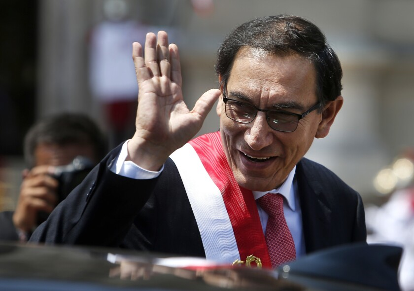 President Martin Vizcarra waves Friday as he makes his way to the House of Pizarro, the presidential residence and workplace, in Lima, Peru.