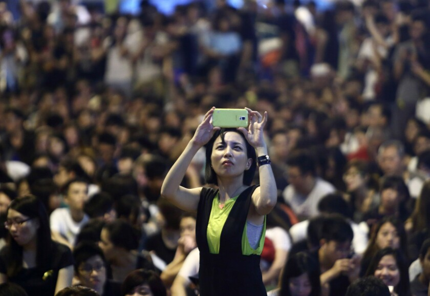 A demonstrator takes a photograph during a protest outside the Central Government Offices in Hong Kong on Oct. 4.