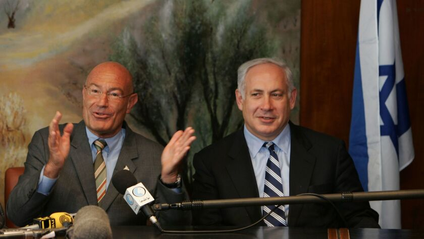 Israeli-American movie producer Arnon Milchan, left, is flanked by then-Finance Minister Benjamin Netanyahu as he announces his donation of $100 million to establish a new Israeli university, at a news conference on March 28, 2005, in Jerusalem.