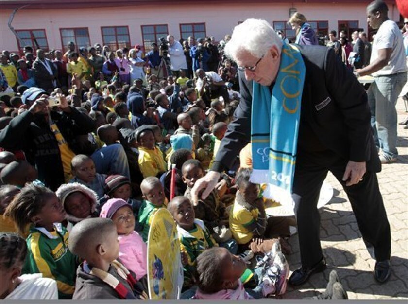 Football Federation Australia (FFA) chairman Mr. Frank Lowy AC right, hands out lap desks to students at Mohlakano Primary in Gauteng, South Africa, Wednesday, June 9, 2010. Lowy announced the Australian Football Federation will donate one million rand for lap desks to the school.(AP Photo/Rob Griffith)