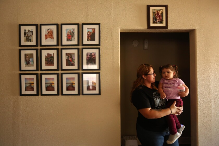 Jessenia Urbina holds her daughter Arielle Urbina, 18 months old, next to family photos