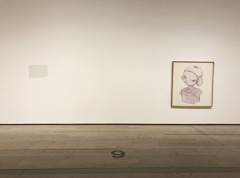 A piece of wall text is located several feet from a painting at LACMA gallery.