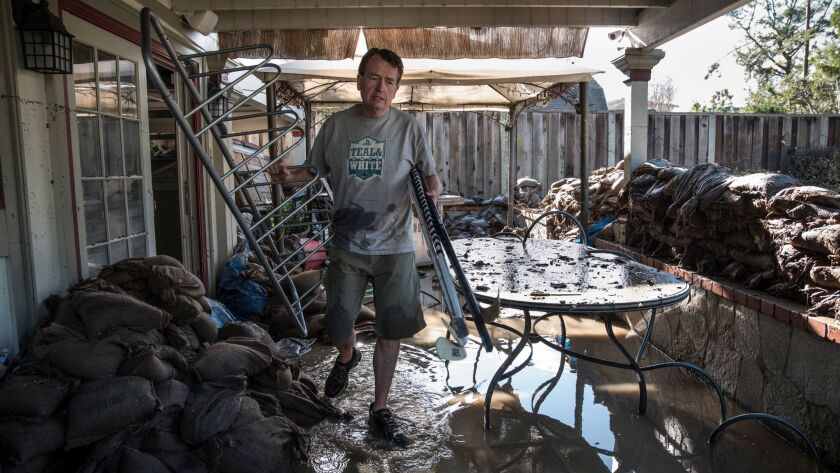 Eric Heckman, who has lived in his house for almost 15 years, clears material from the lower level after the flood.