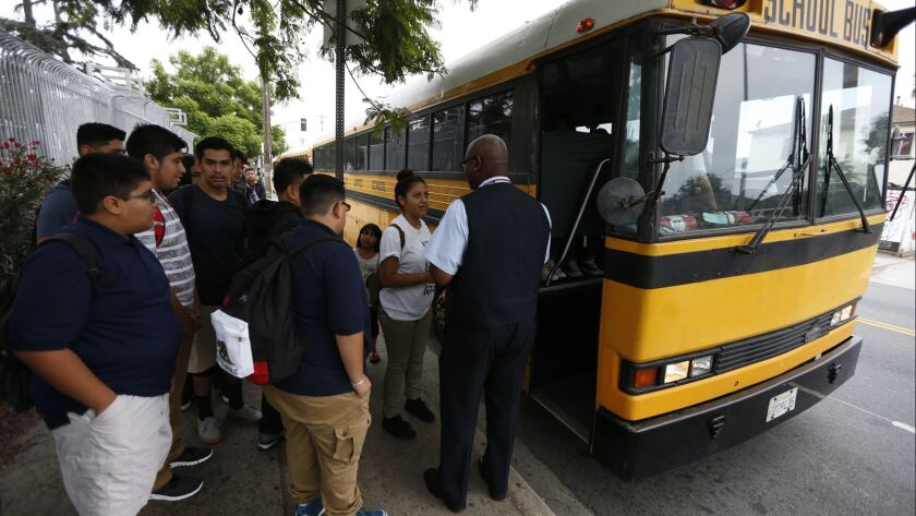 Students line up at a district bus stop next to Jefferson High School in Los Angeles on August 18, 2015.