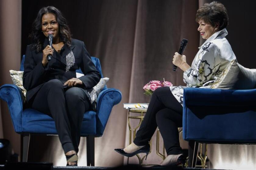 US former first lady Michelle Obama (L) chats with long-time friend Valerie Jarrett during a book tour event at the Capital One Arena in Washington on Saturday, Nov. 17. EFE-EPA/SHAWN THEW