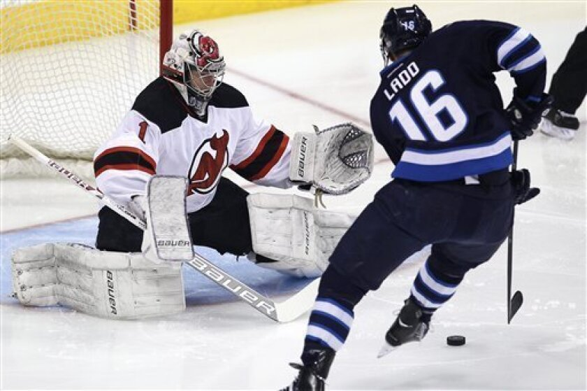 Winnipeg Jets' Andrew Ladd (16) scores on New Jersey Devils goaltender Johan Hedberg (1) in the opening seconds of an NHL hockey game in Winnipeg, Manitoba, on Thursday, Feb. 28, 2013. (AP Photo/The Canadian Press, John Woods)
