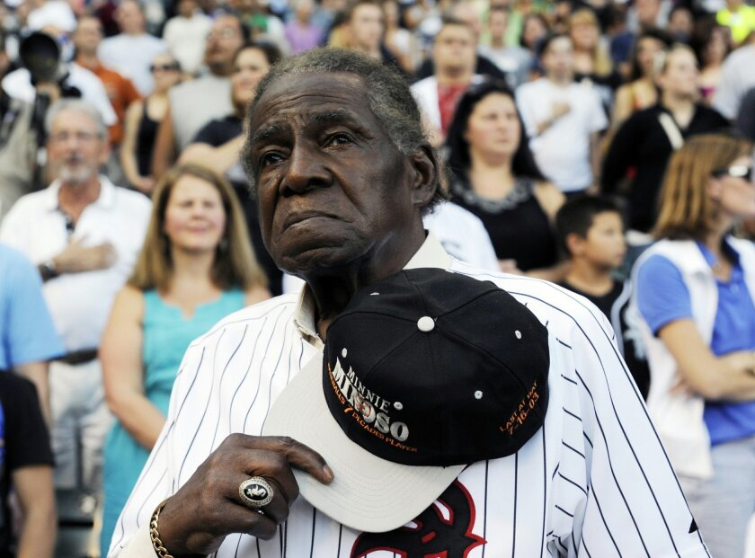 FILE - In a Aug. 24, 2013 file photo, former Negro Leaguer and Chicago White Sox player Minnie Minoso stands during the national anthem before a baseball game between the Chicago White Sox and the Texas Rangers, in Chicago.  Major league baseball's first black player in Chicago, Minnie Minoso, has