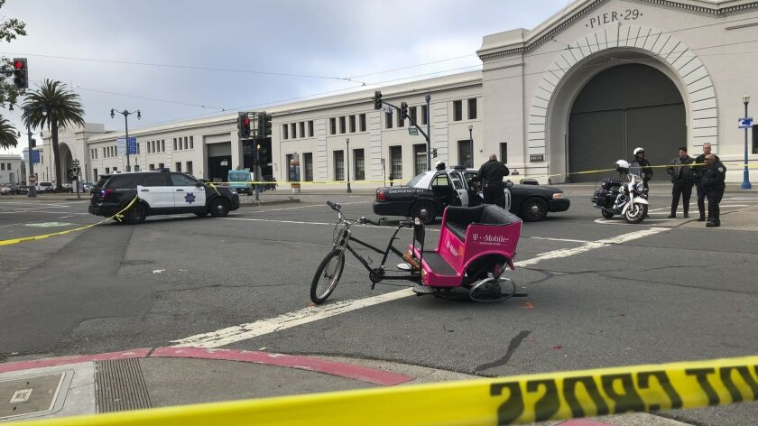 A crashed pedicab sits in the street in San Francisco on Wednesday after authorities said a hit-and-run driver crashed into it, injuring several people.