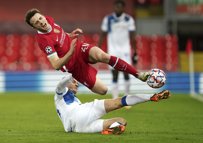 Liverpool's Diogo Jota is tackled by Atalanta's Marten de Roon during the Champions League group D soccer match at Anfield stadium in Liverpool, England on Nov. 25, 2020. (AP Photo/Jon Super)