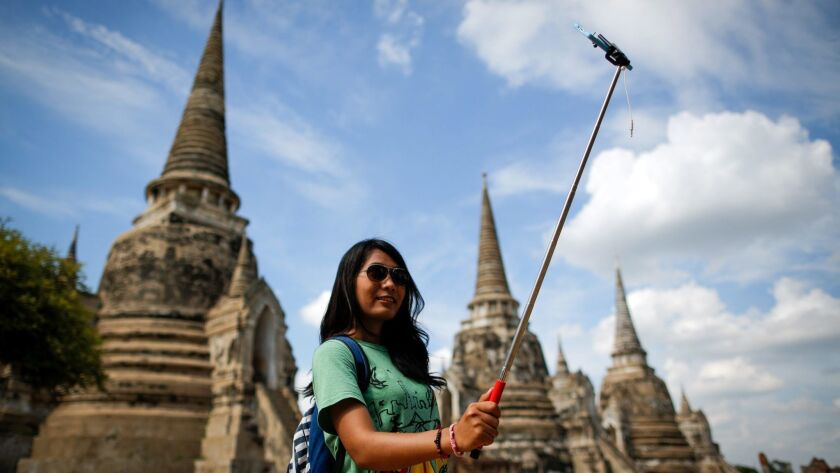 A tourist takes a selfie at Wat Phra Si San Phet, one of the many temples in the ancient historical city of Ayutthaya, Thailand.