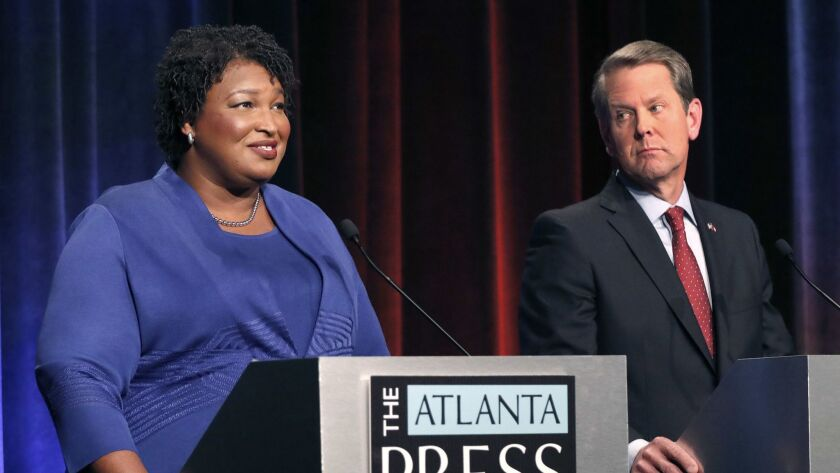 Democratic gubernatorial candidate for Georgia Stacey Abrams, left, speaks as her Republican opponent Secretary of State Brian Kemp looks on during a debate in Atlanta on Tuesday.