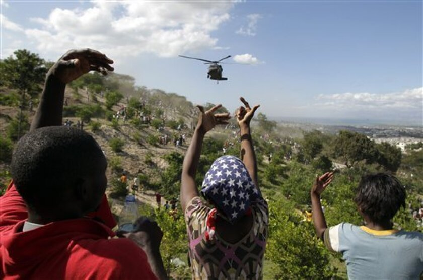 People gestures as a U.S. helicopter makes a water drop near a country club used as a forward operating base for the U.S. 82nd Airborne Division in Port-au-Prince, Haiti, Saturday, Jan. 16, 2010.  Relief groups and officials are focused on moving aid flowing into Haiti to survivors of the powerful