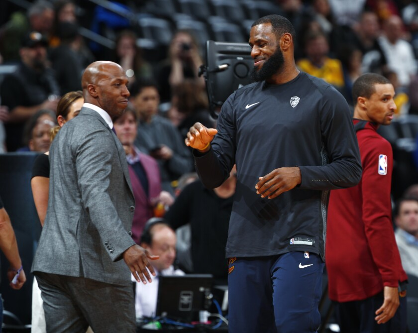 LeBron James greets broadcaster and retired NBA player Chauncey Billups during a Cavaliers playoff game in 2018.