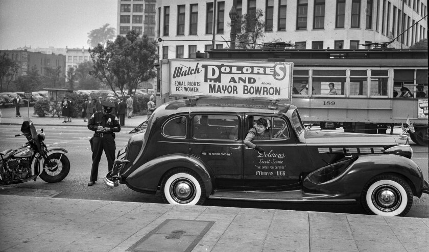 June 9, 1943: Dolores Gunn waits as Los Angeles Police officer writes up a parking ticket. Gunn, pro