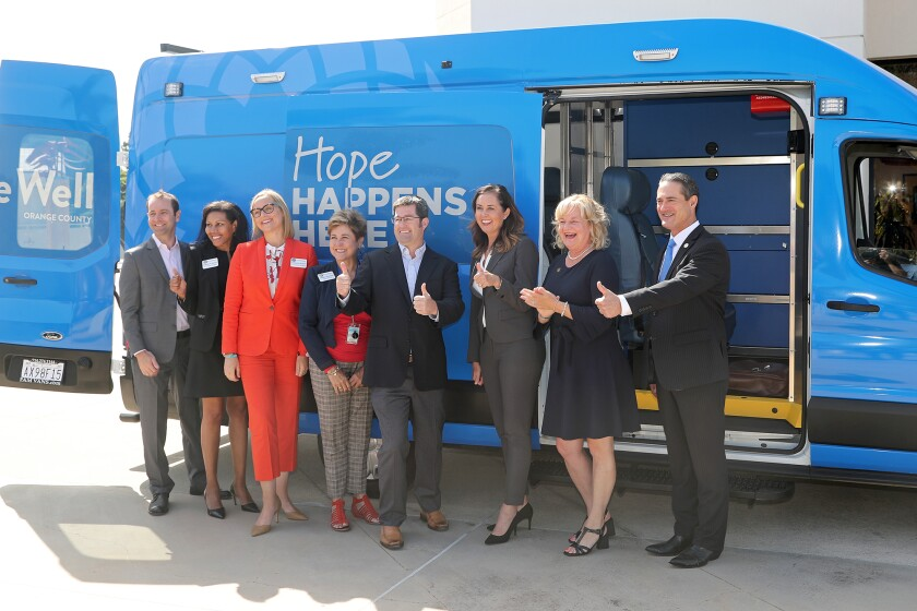 Elected officials stand in front of a Be Well OC mobile vehicle at Huntington Beach Civic Center Plaza.