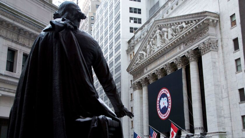 A statue of George Washington overlooks the New York Stock Exchange, which bears a banner for down-jacket maker Canada Goose.