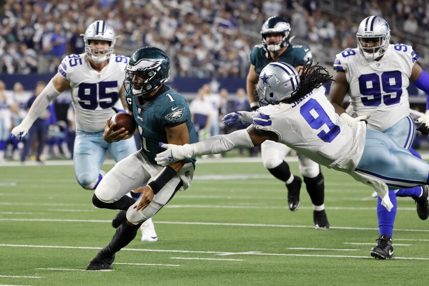 Philadelphia Eagles quarterback Jalen Hurts (1) runs the ball as Dallas Cowboys linebacker Jaylon Smith (9) attempts to make the stop in the second half of an NFL football game in Arlington, Texas, Monday, Sept. 27, 2021. (AP Photo/Michael Ainsworth)