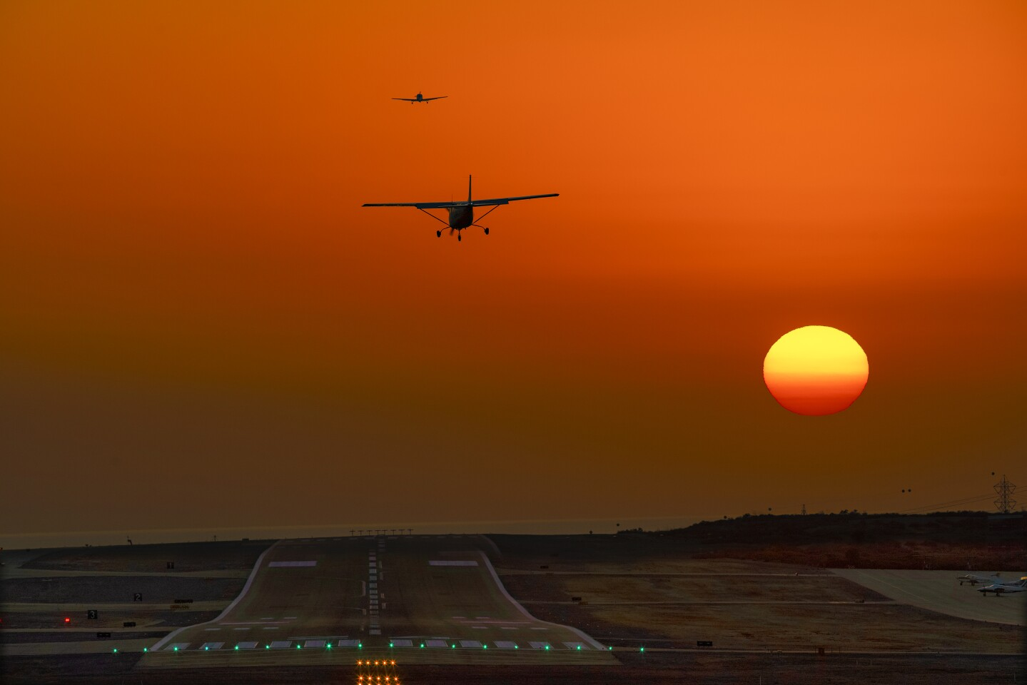Two small aircrafts fly above the runway at Palomar Airport in Carlsbad during an October sunset.